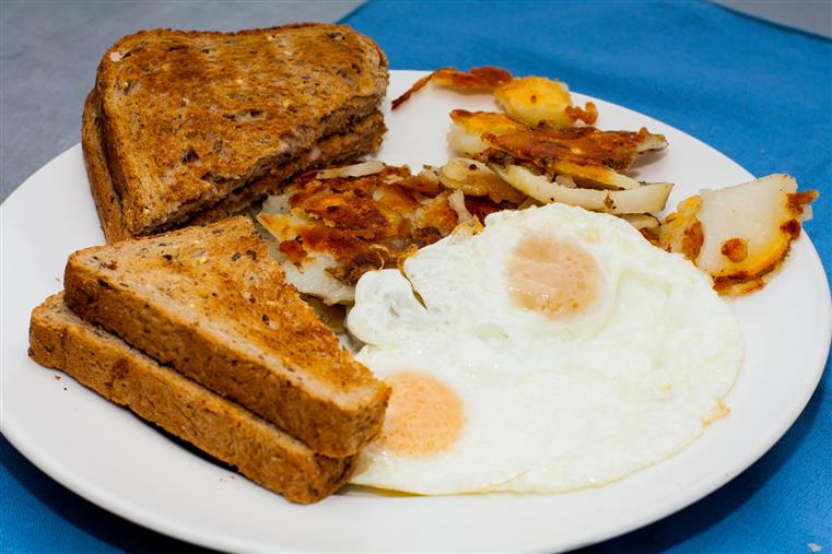 two eggs cooked over-medium with a side of hashbrowns and multigrain toast