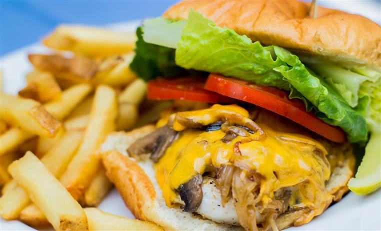 cheeseburger on a bun with melted cheese, sauteed mushrooms and onions, tomatoes and lettuce, side of french fries