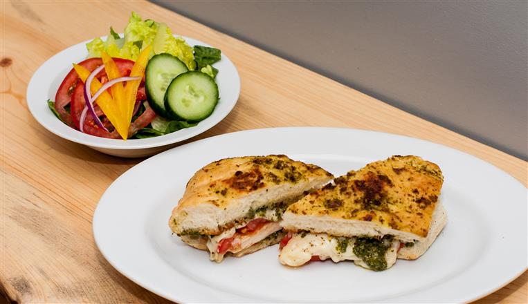 panini with melted mozzarella, pesto, and roasted red peppers on fociccia bread with a side salad