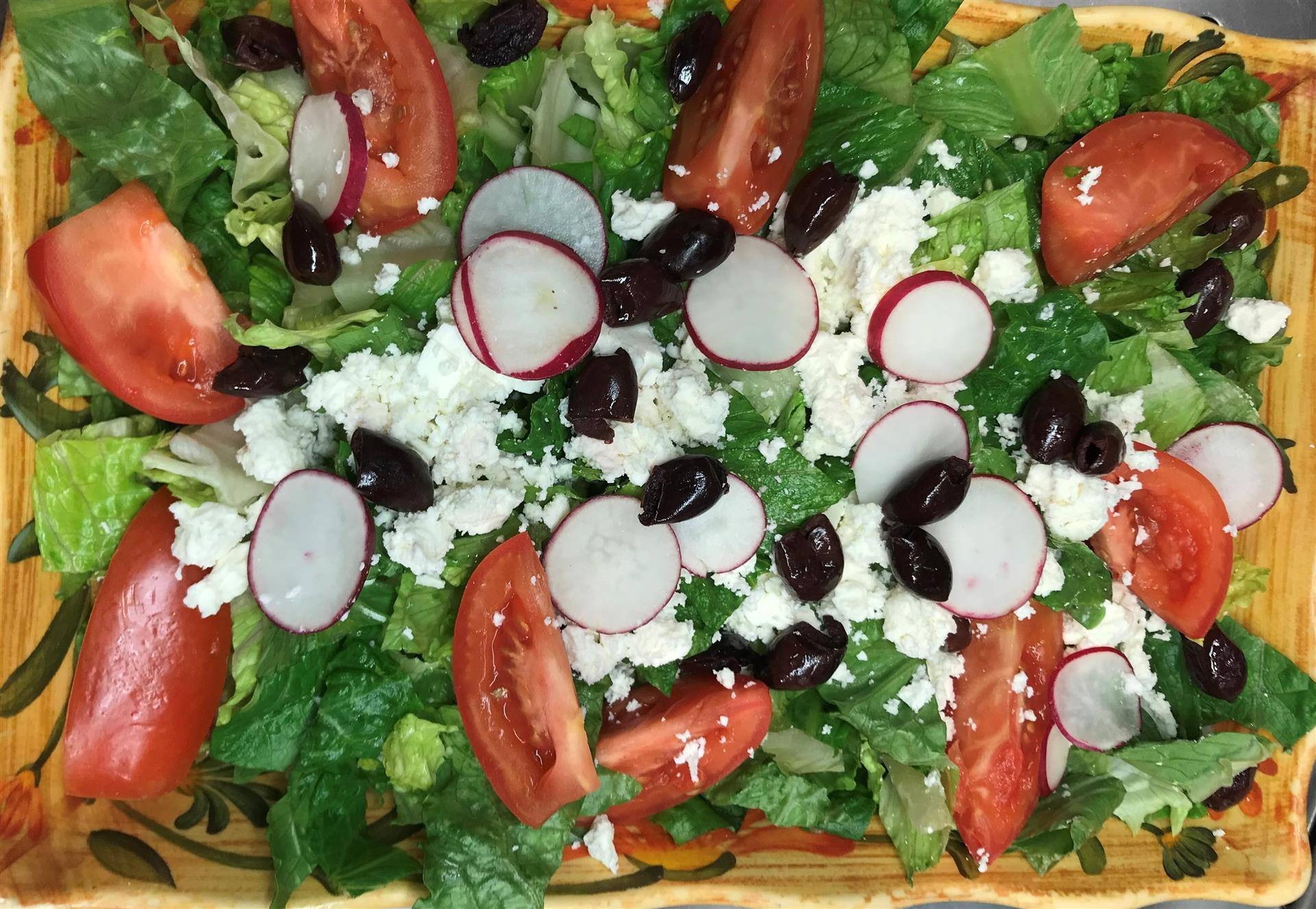 greek salad with feta, kalamata olives, tomatoes and radishes