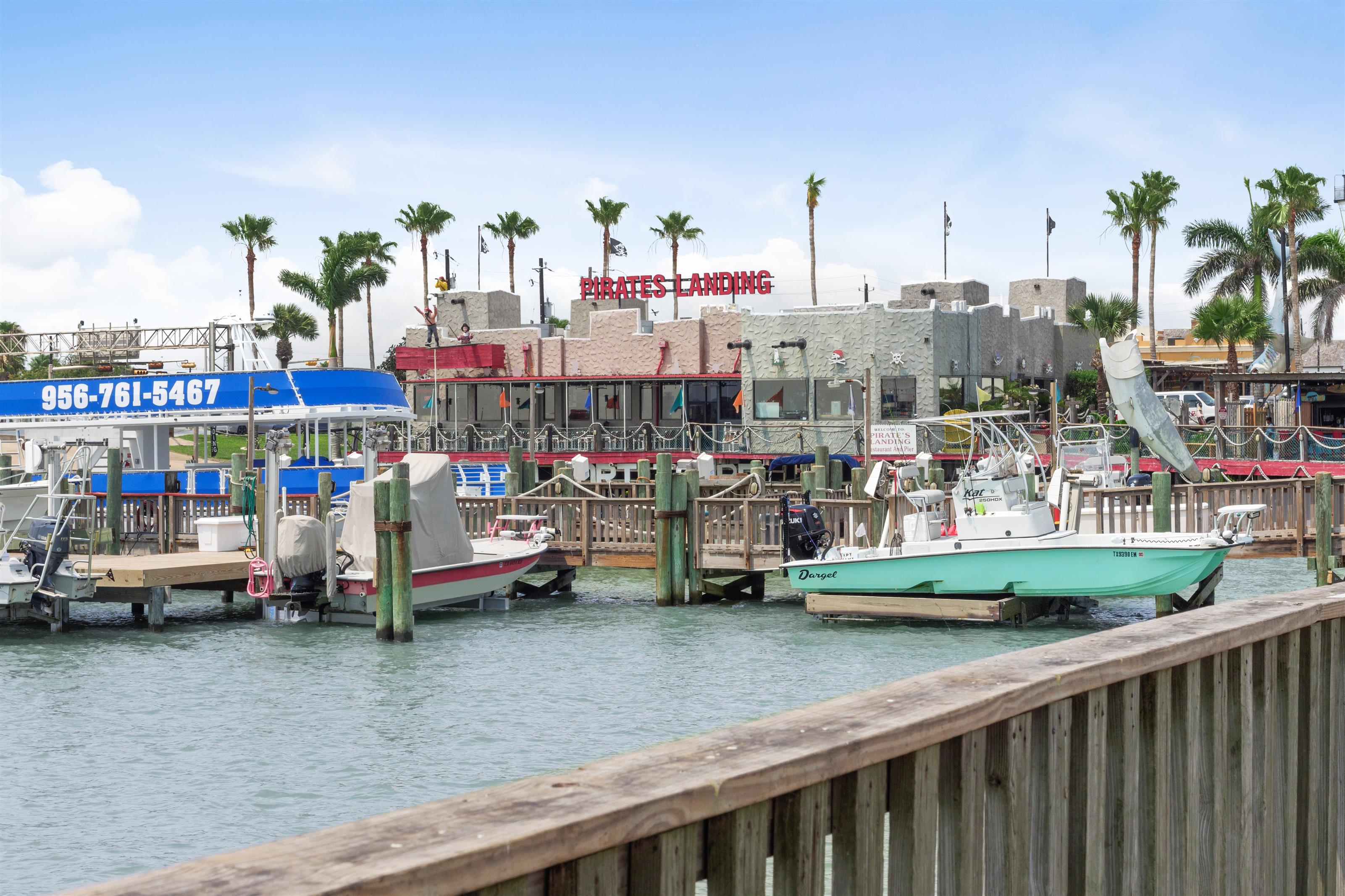 view of the restaurants on the Pier from the boardwalk, boats docked in harbor