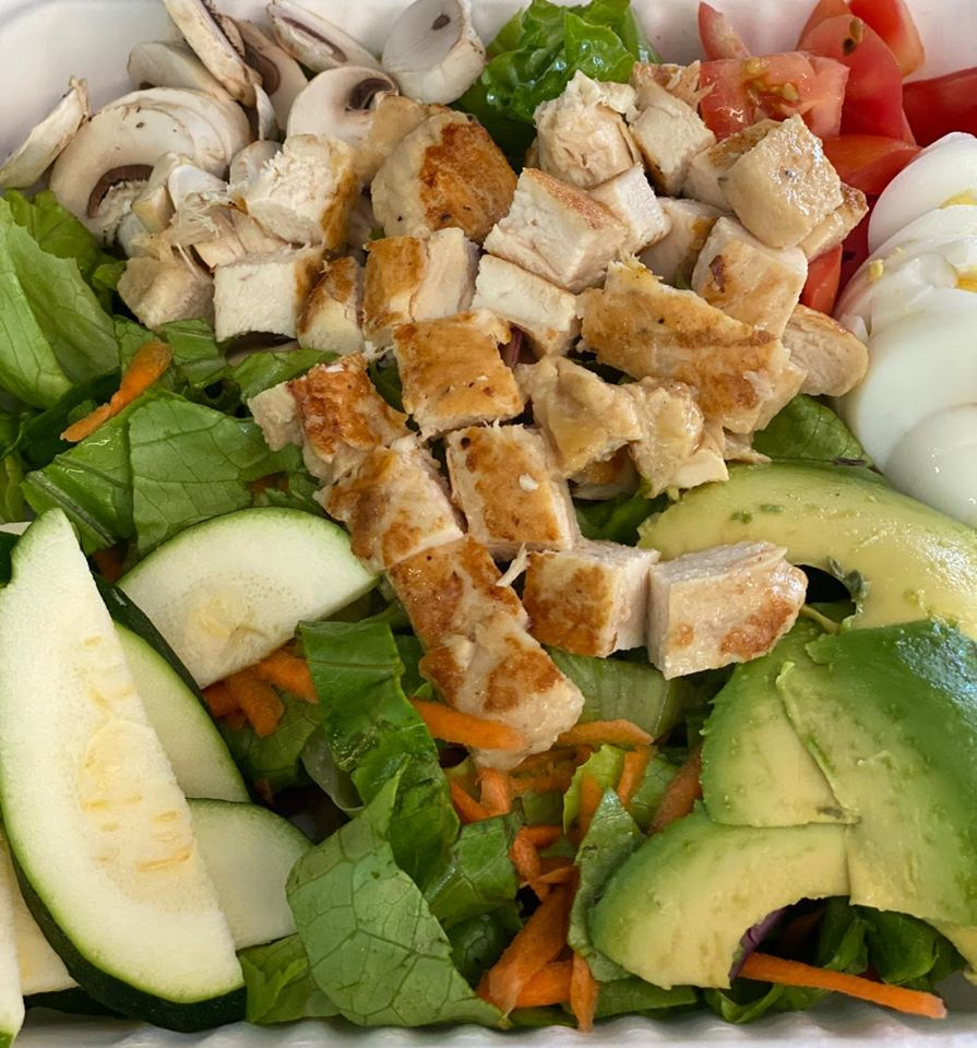 A salad topped with avocado, cucumber, tomato, hard boiled egg, mushroom, and grilled chicken
