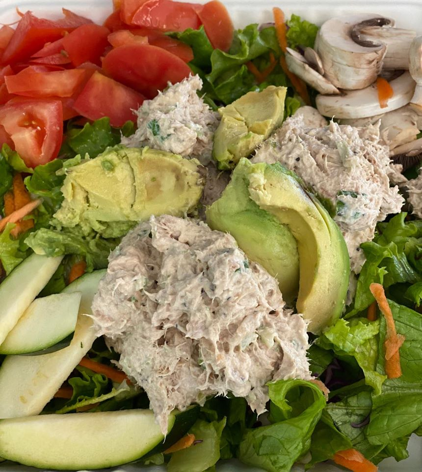 A salad topped with tuna, avocado, tomato, mushroom, and apple slices