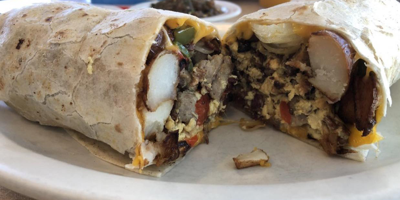 A breakfast burrito with eggs, tomato, beans, and bacon