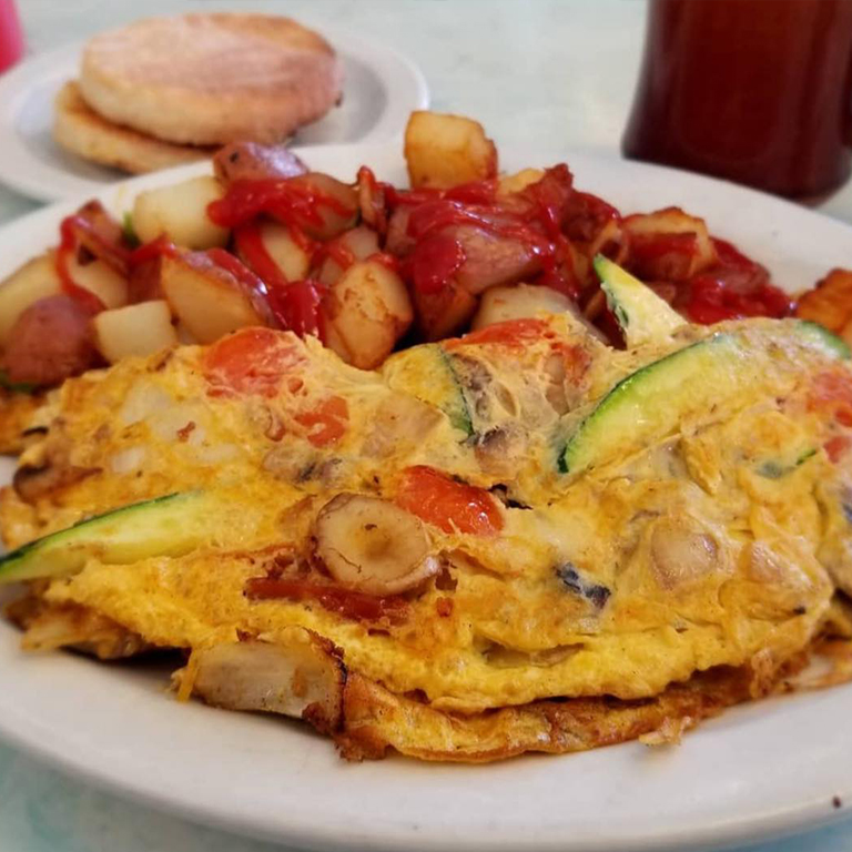 An omelet with peppers and a side of potatoes