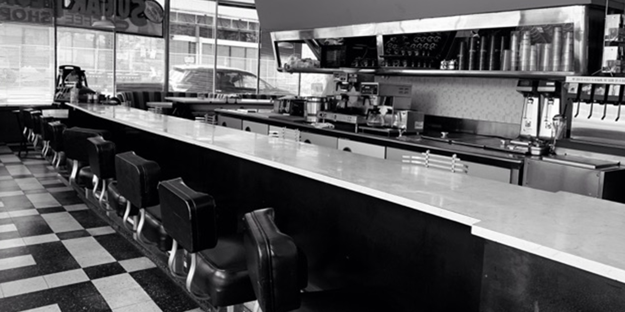The bar with empty seats and the vintage checkered floor