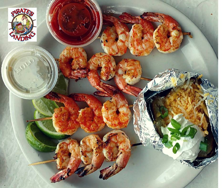 four shrimp skewers with a cheesy baked potato and sides of sauce