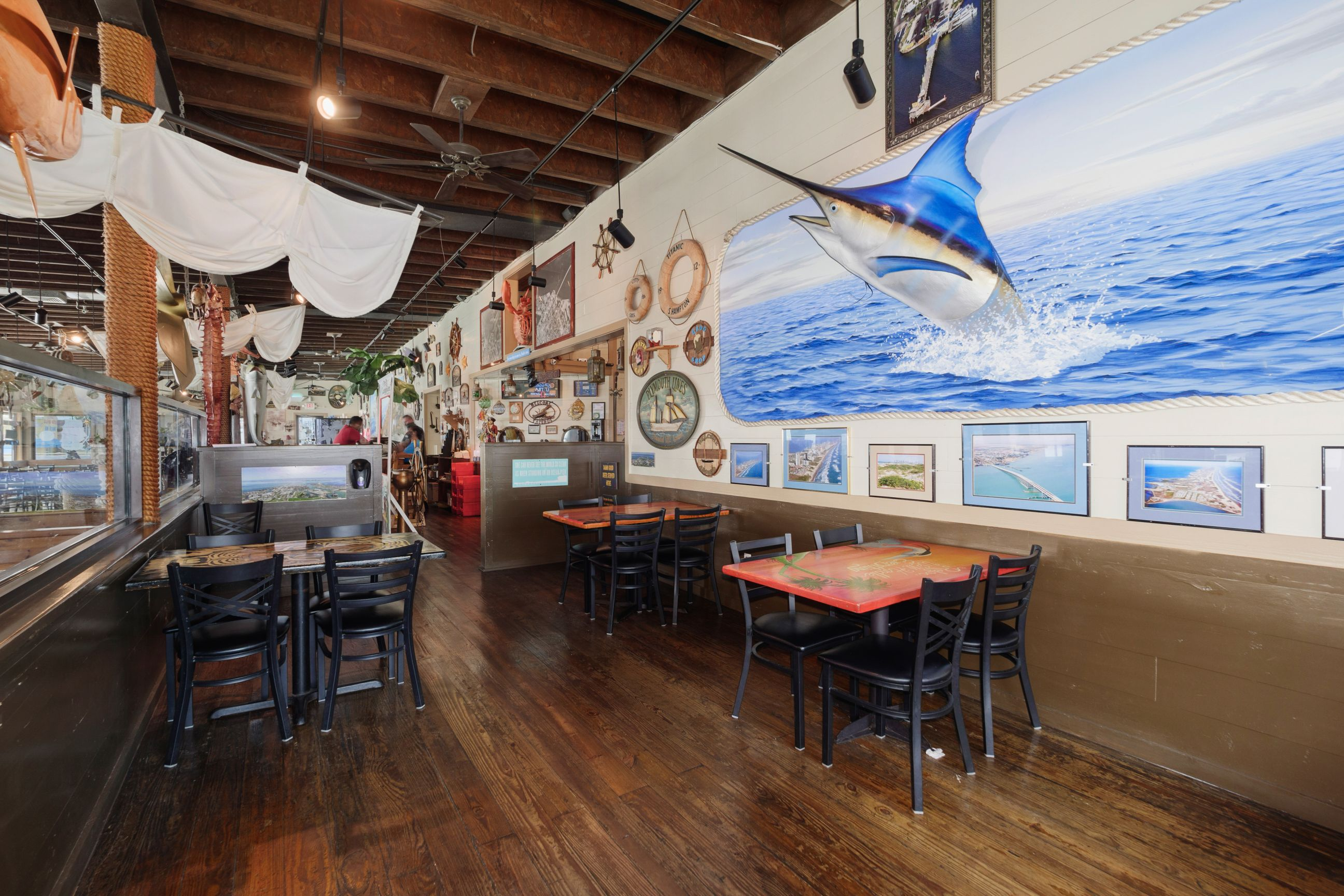 interior seating at restaurant with mural of a Marlin