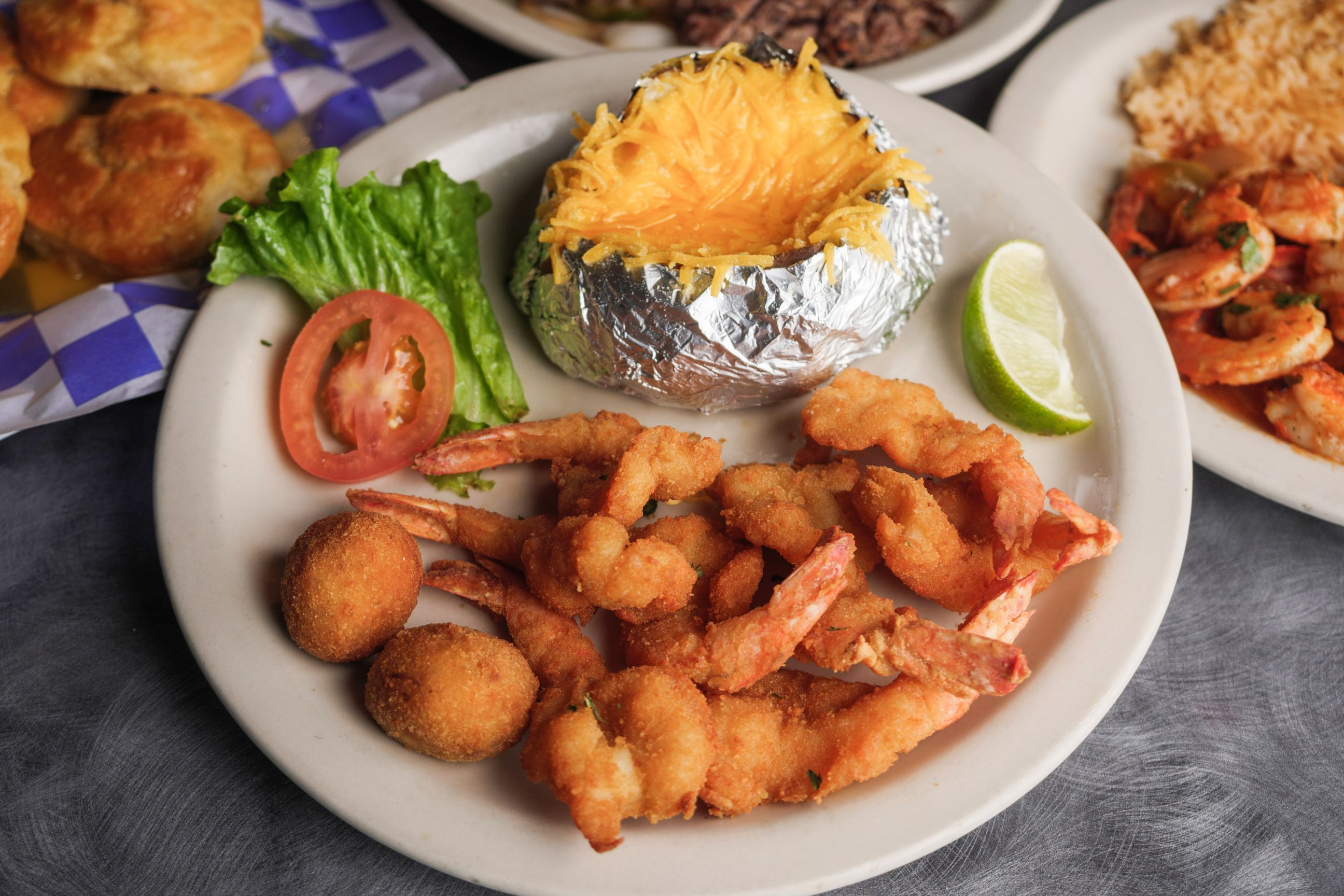 fried shrimp, hush puppies, cheesy baked potato on a plate with lettuce, tomato slice, and lime wedge