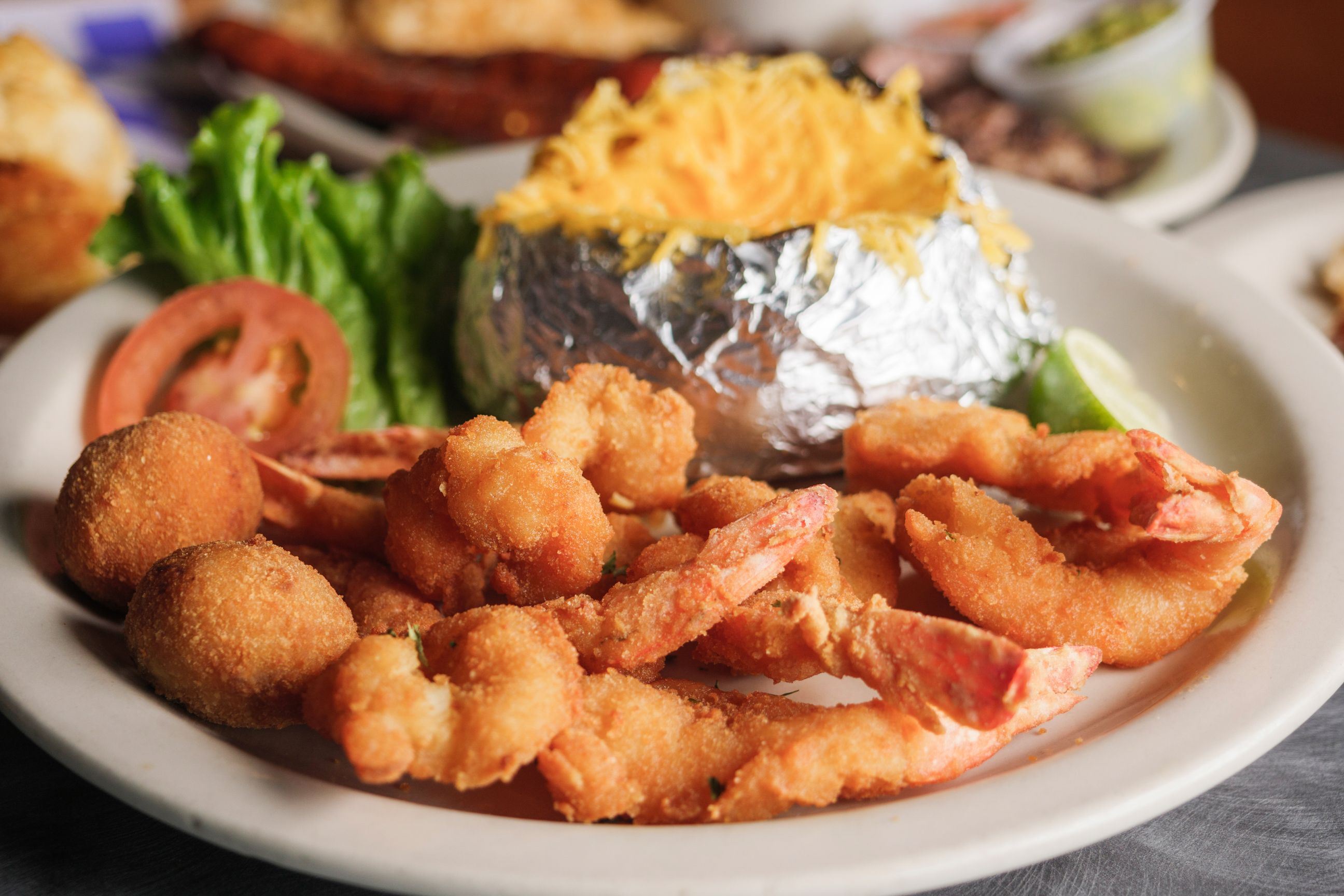 Popcorn shrimp with hush puppies, cheesy baked potato, and slice of tomato and lettuce