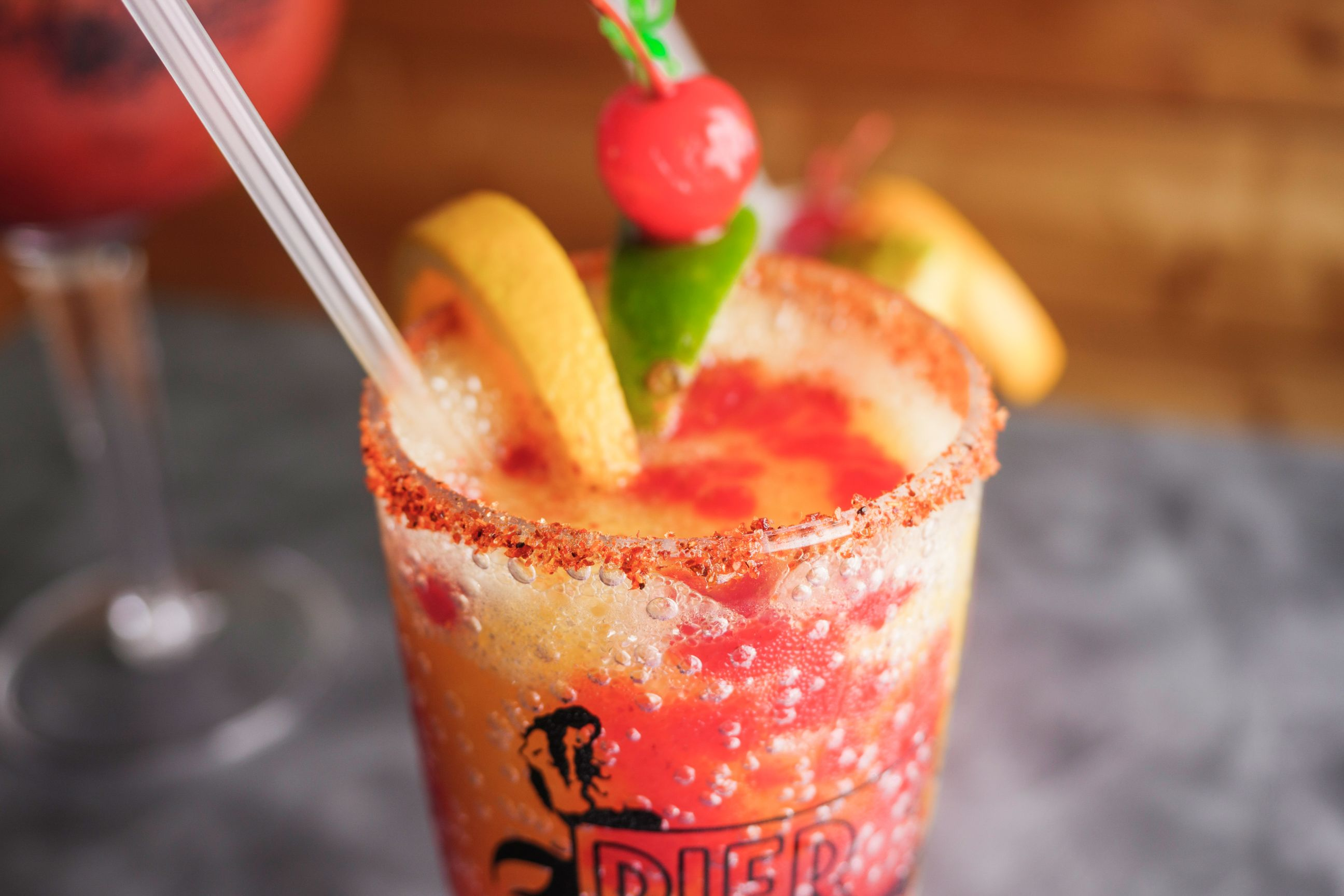 tropical cocktail with chili powder rim, garnished with lemon, lime and cherry