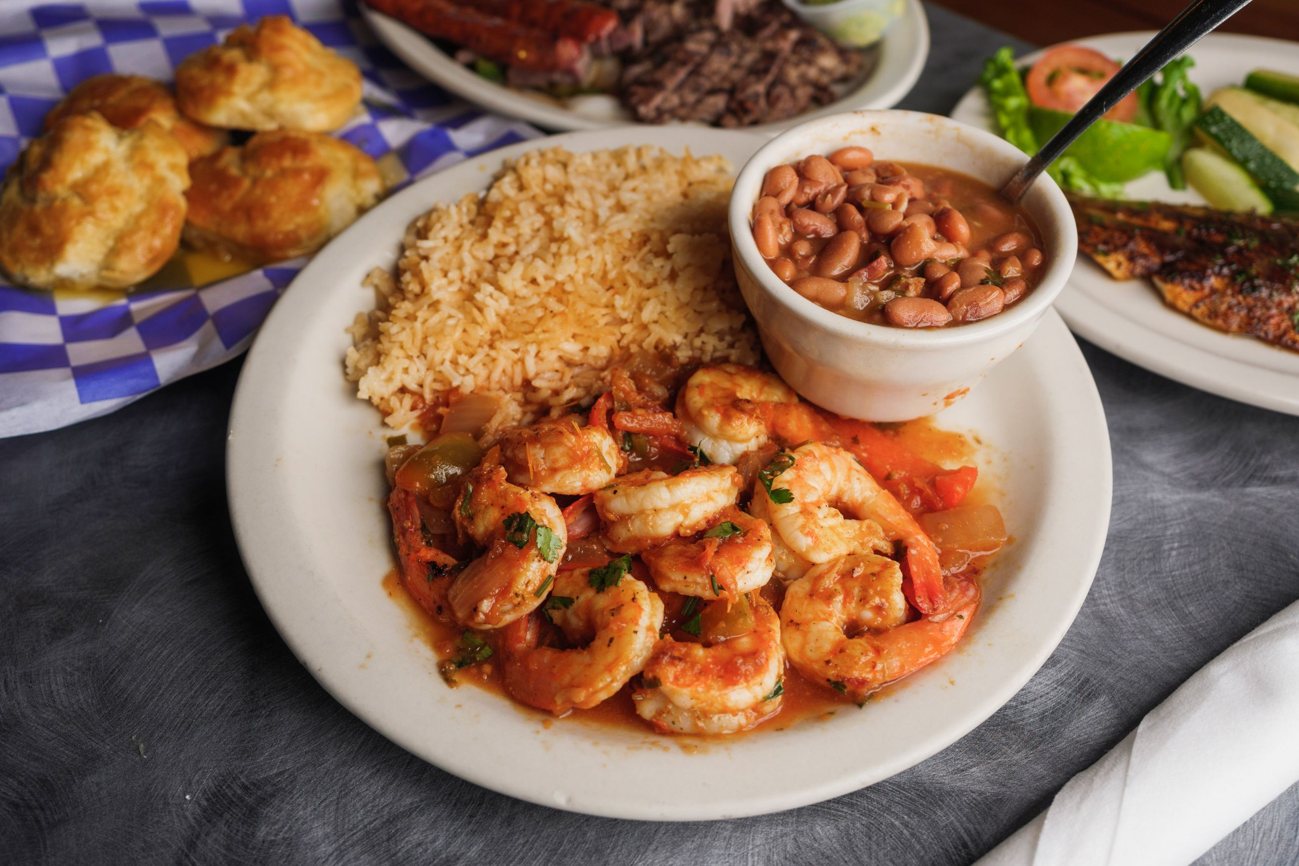 plate of shrimp, rice and baked beans with other entrees on a table
