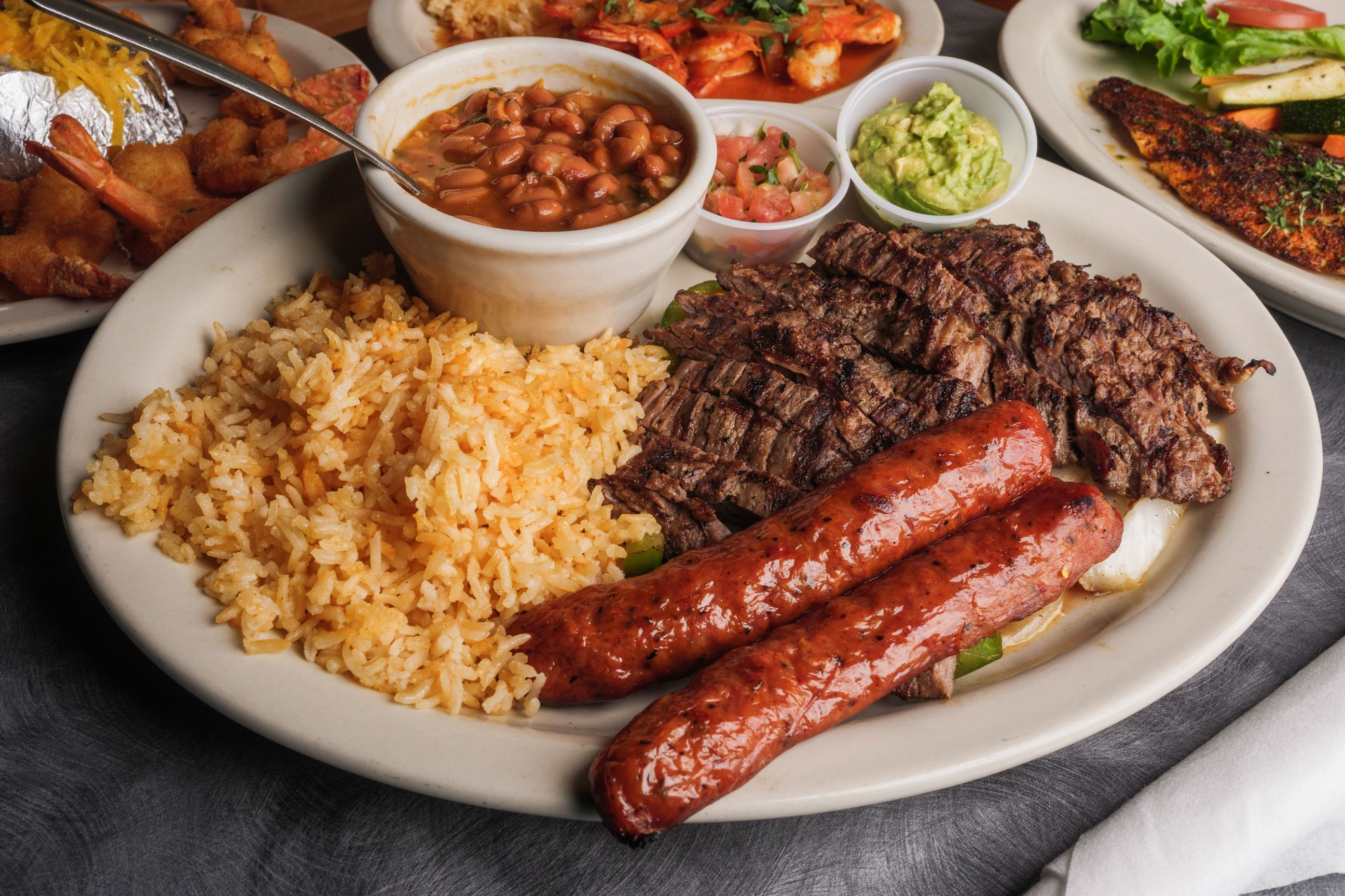 platter of rice, baked beans, beef, and sausage with cups of salsa and guacamole