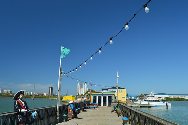 view of the Pier with painted benches, string lights, and a flag pole
