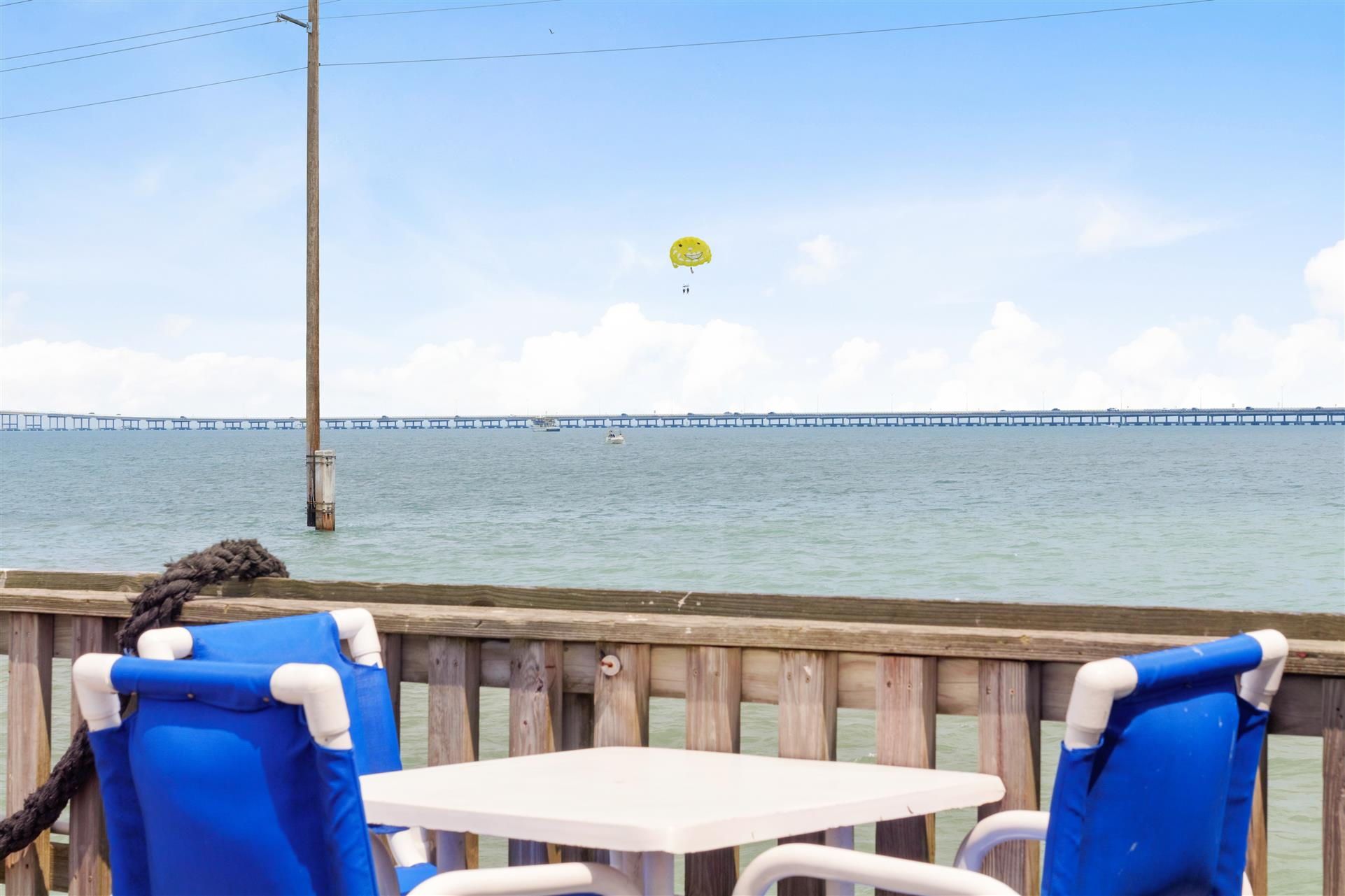 outside dining table with view of parasailer over the water