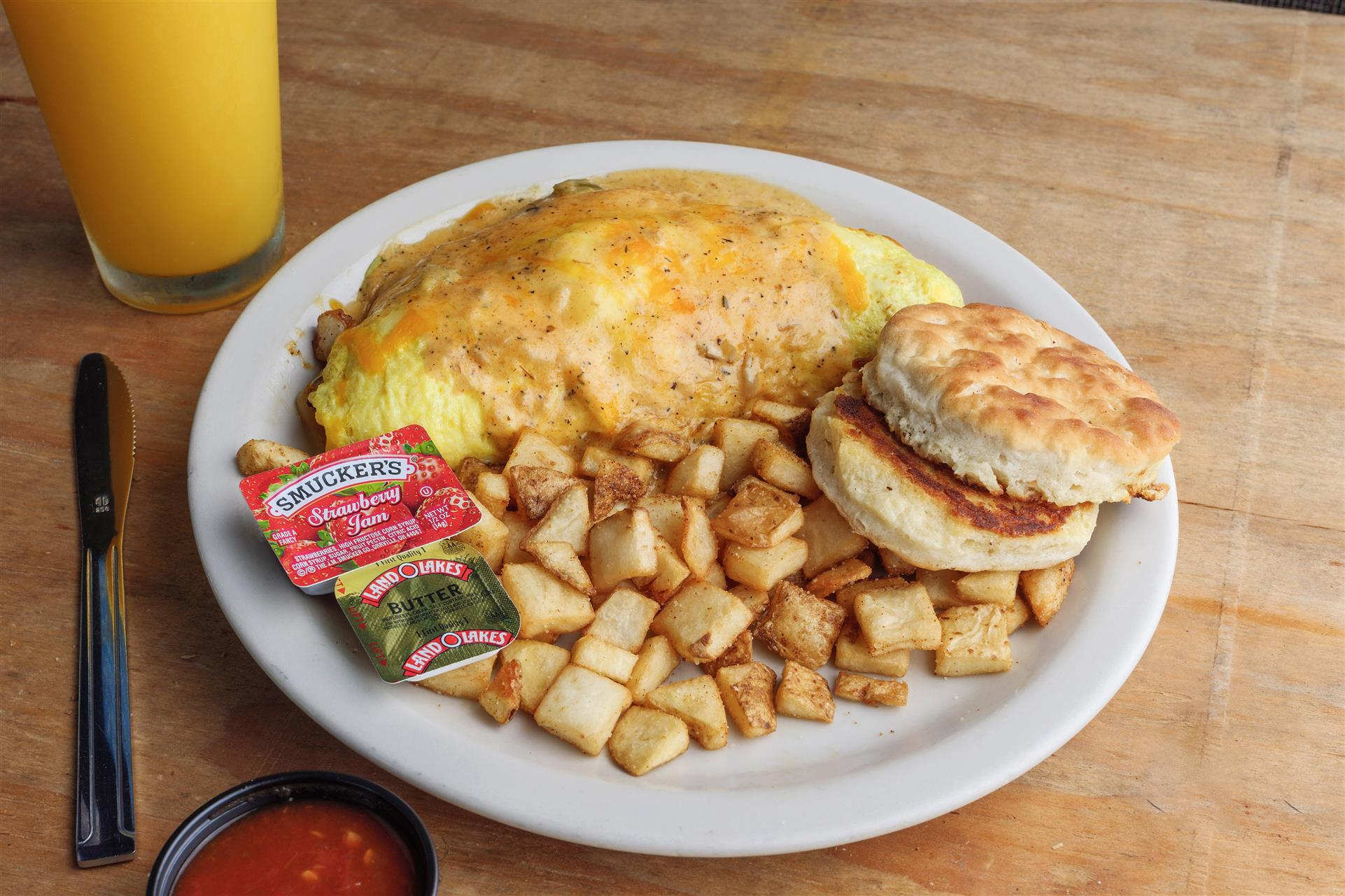 large omelette with melted cheese, side of home fries and biscuits, glass of orange juice