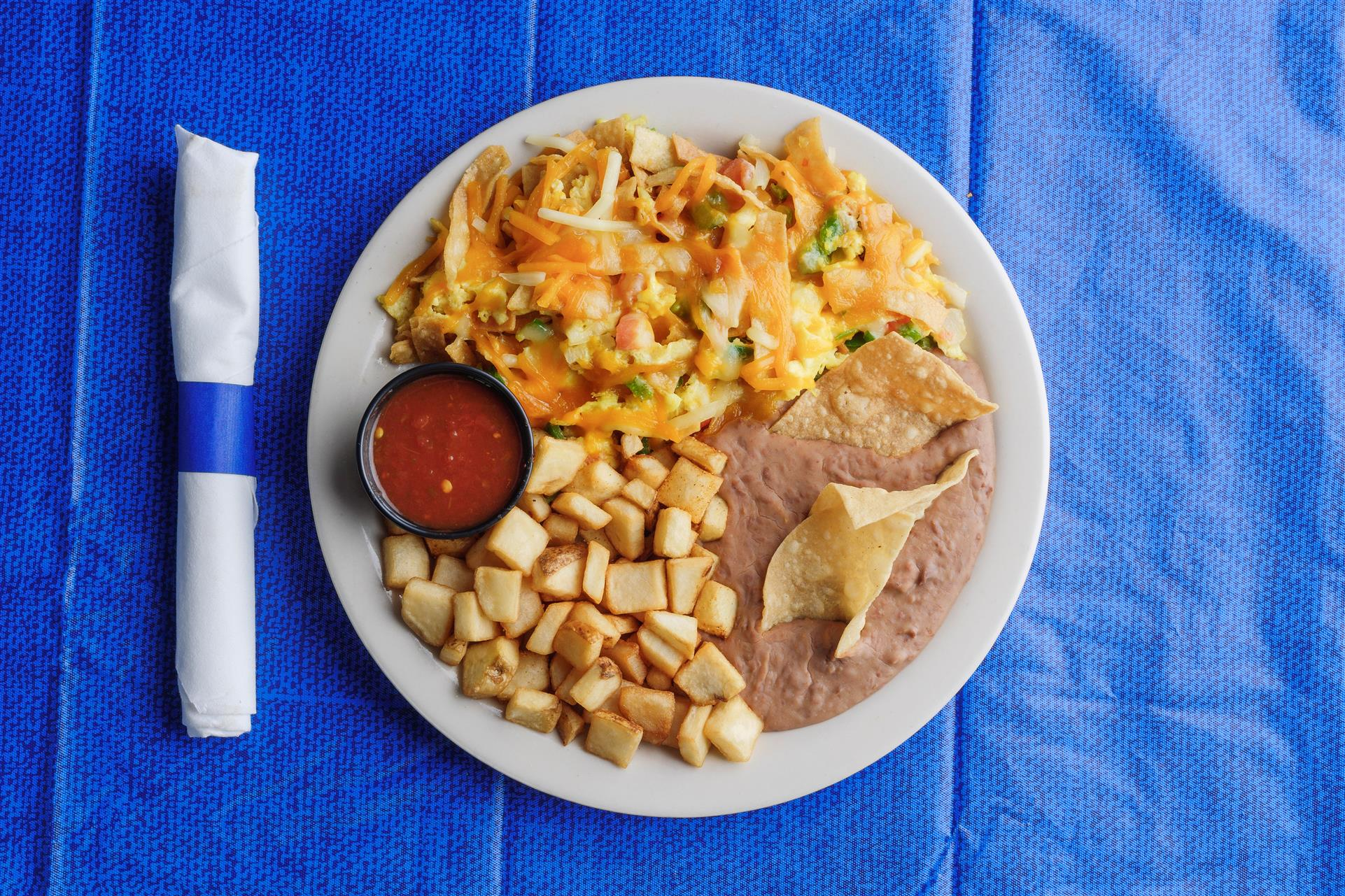 mexican-style breakfast scramble with sides of home fries, salsa, and refried beans with tortilla chips