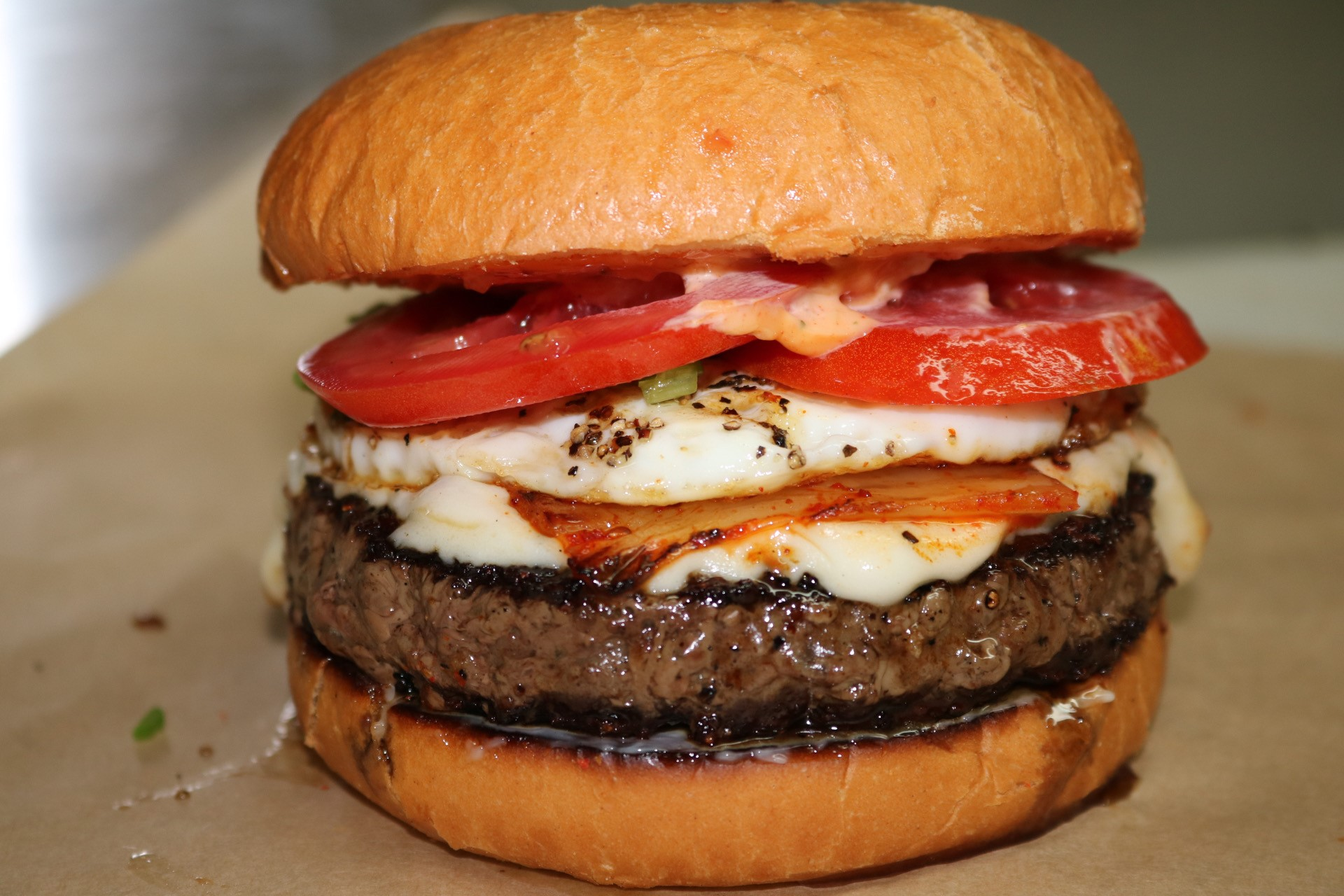 cheeseburger with fried egg, tomato, onion, and sauce