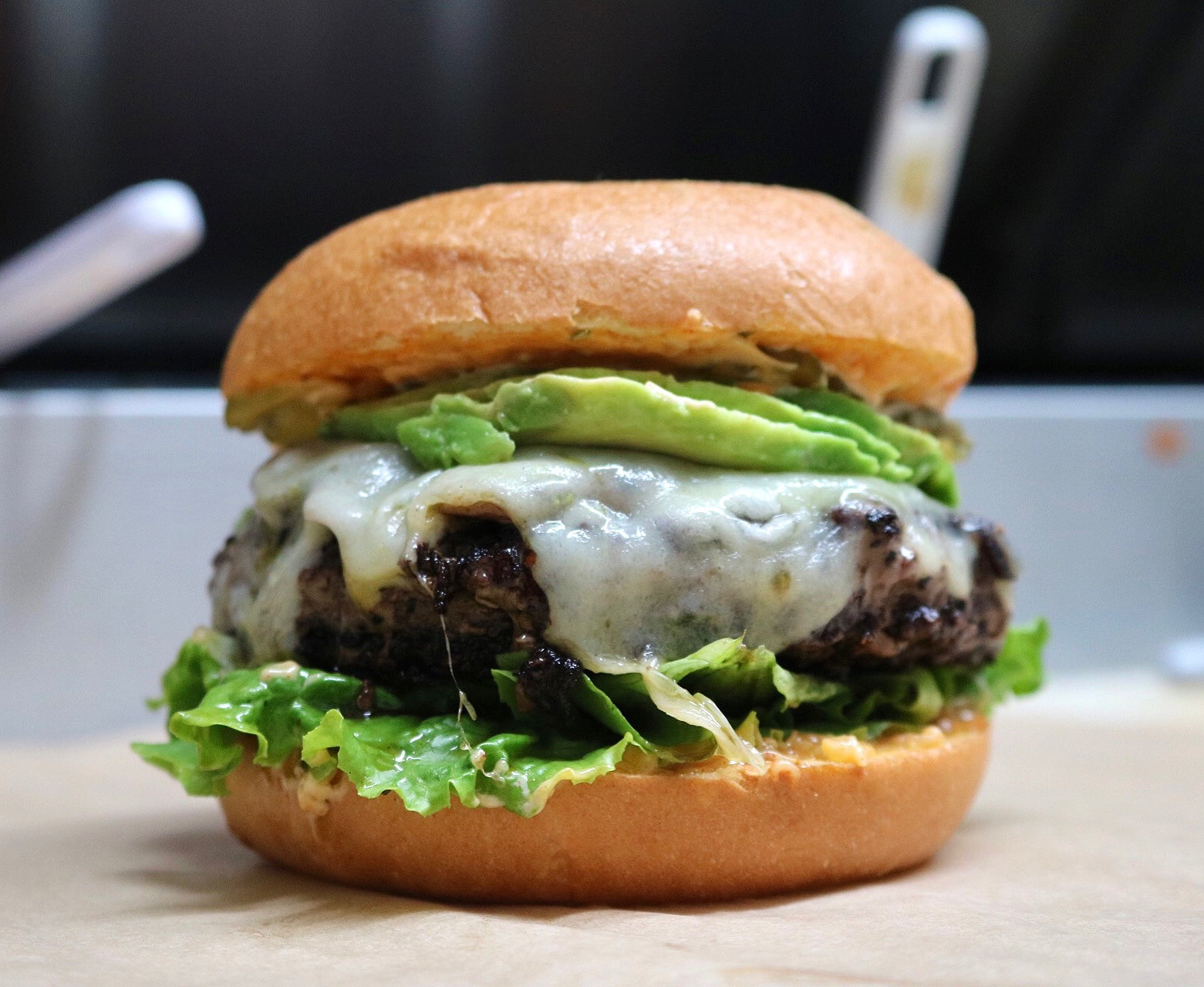 burger with cheese, lettuce, sauce and avocado