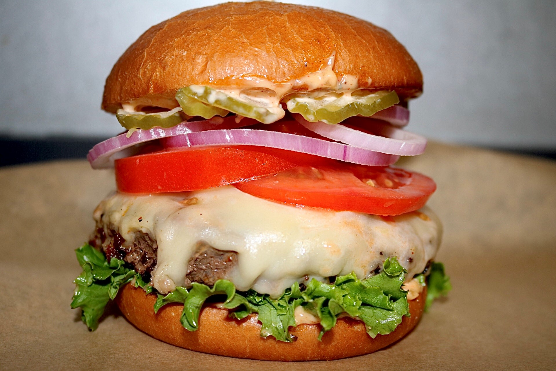 burger with melted cheese. red onion, tomato, lettuce, pickles and spicy sauce