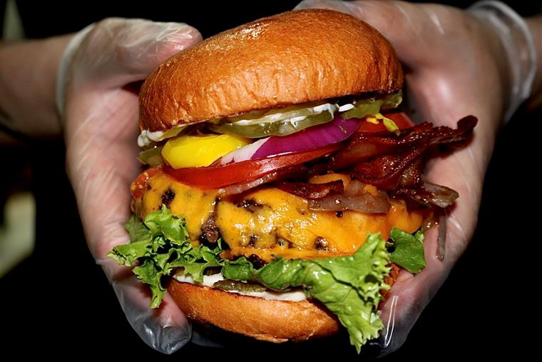 cheeseburger with bacon, lettuce, Hidden sauce, pickles, carmelized onions, and banana peppers