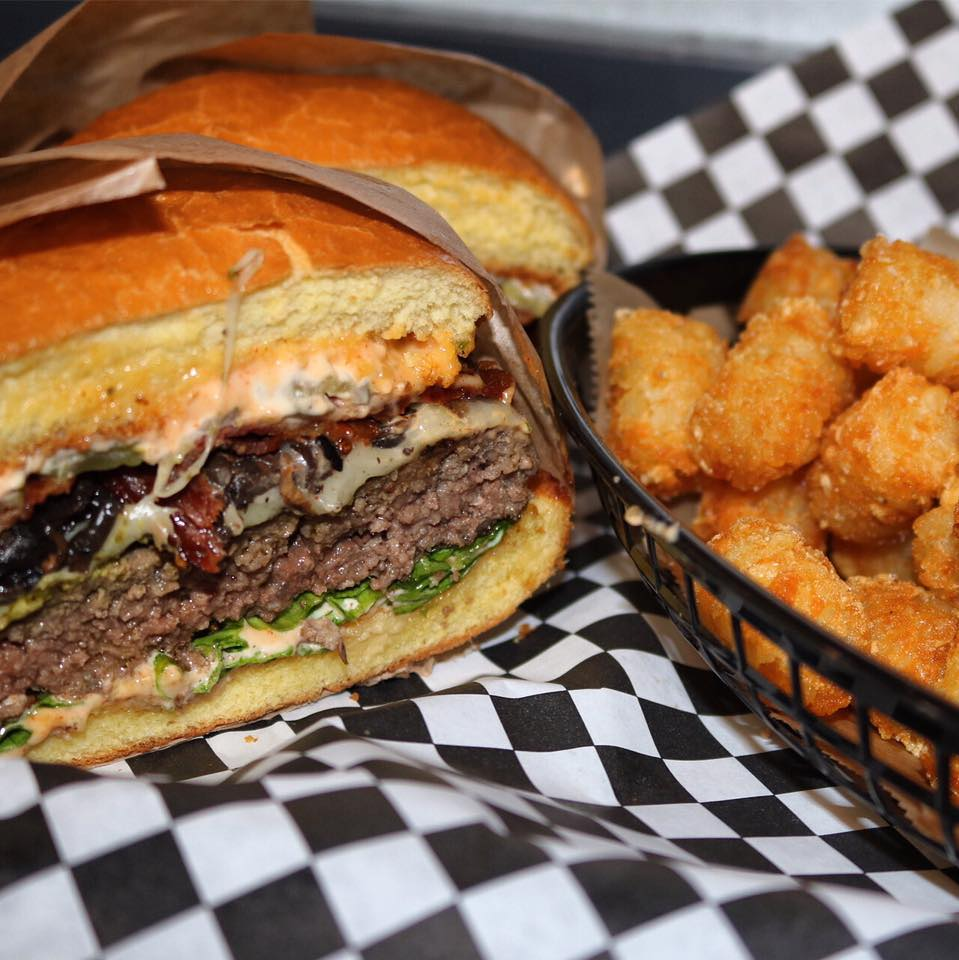 cheesebuger cut in half with bacon, sauteed onions, lettuce, and spicy sauce, side of tater tots