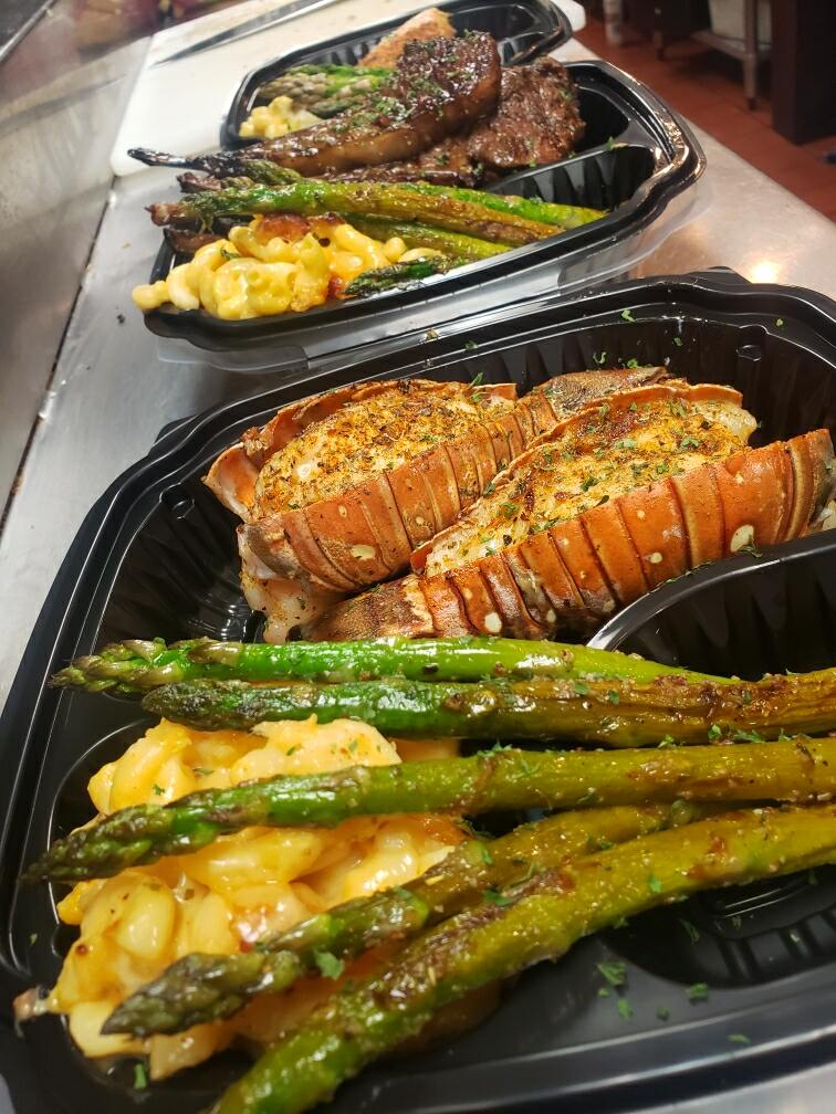 lobster and lamb in plastic to-go containers with sides of asparagus and mac n cheese