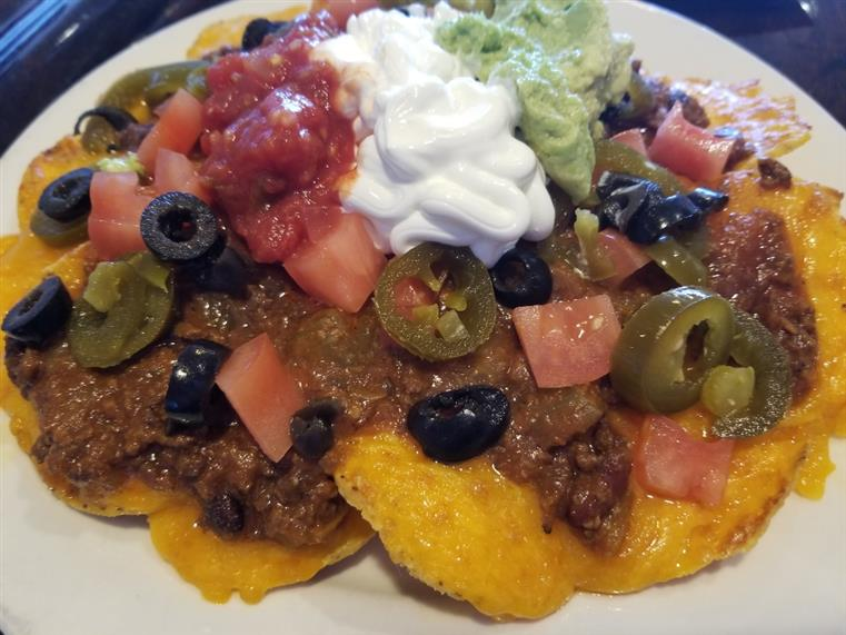 beef nachos with cheese, tomatoes, jalapenos, olives sour cream and salsa