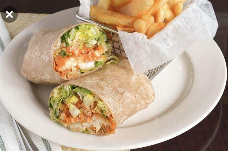 fried chicken wrap with lettuce and tomato served with fries on the side