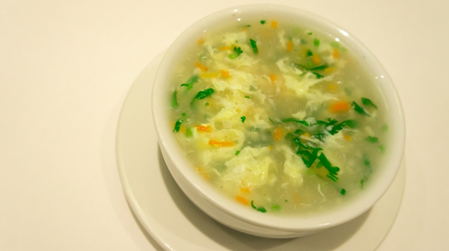 bowl of wonton soup with carrots and scallions