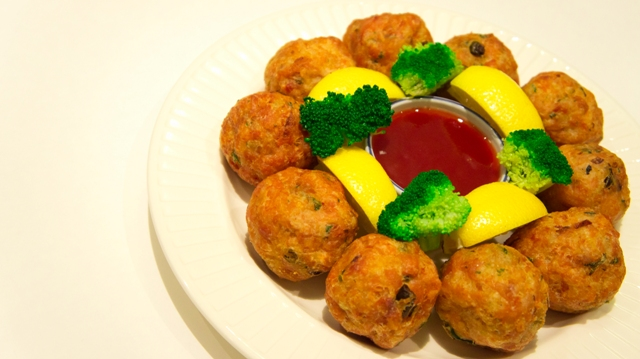 fried rice balls with vegetables, garnished with broccoli and lemon, cup of dipping sauce