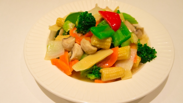 bowl of steamed vegetables, including baby corn, broccoli, peppers, carrots, and mushrooms