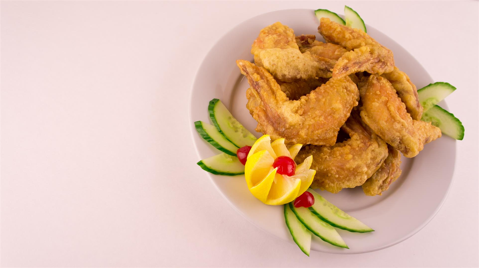 plate of fried chicken wings, garnished with lemon and cucumber