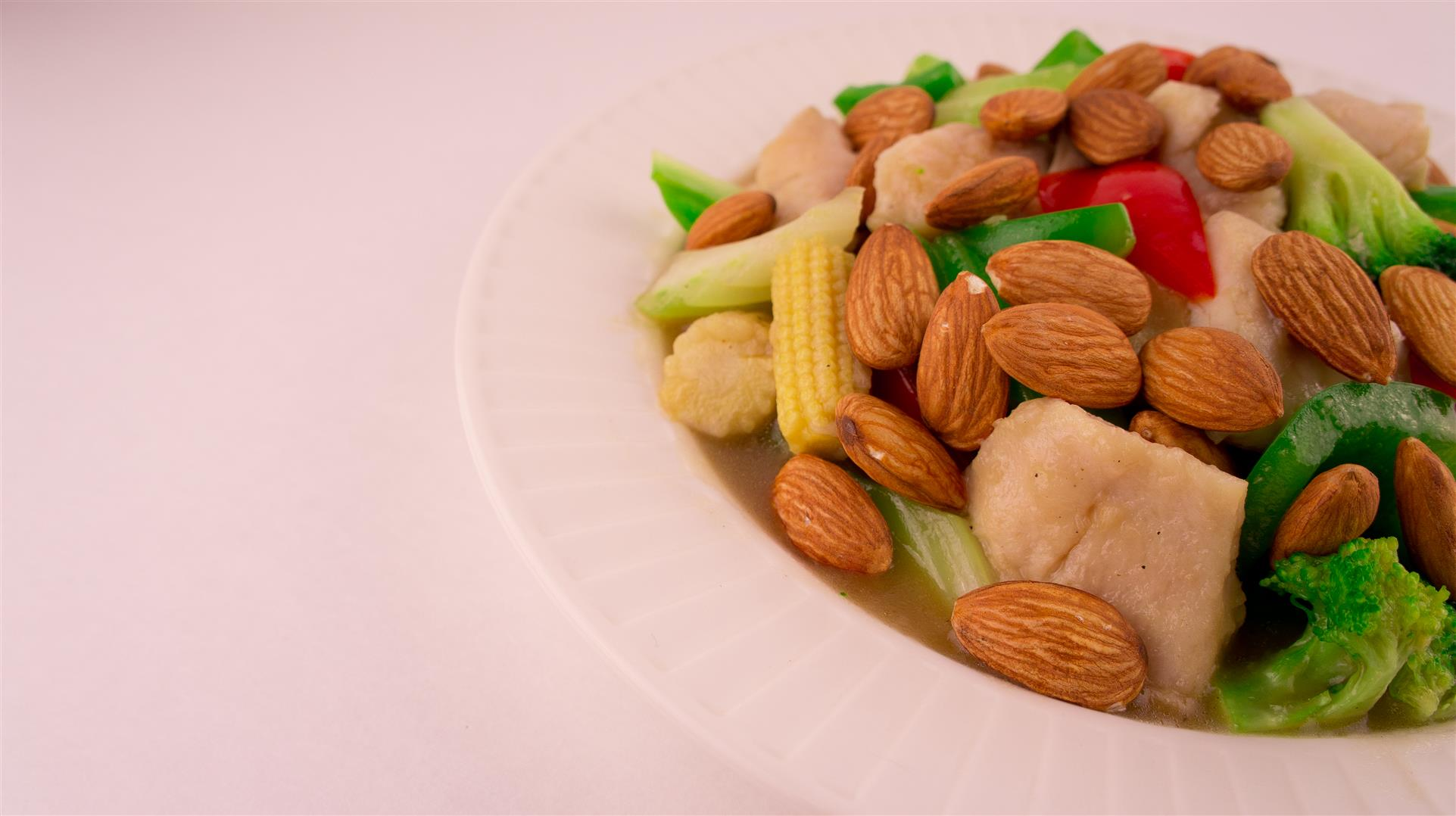 bowl of steamed chicken, broccoli, peppers, onions, baby corn, and almonds