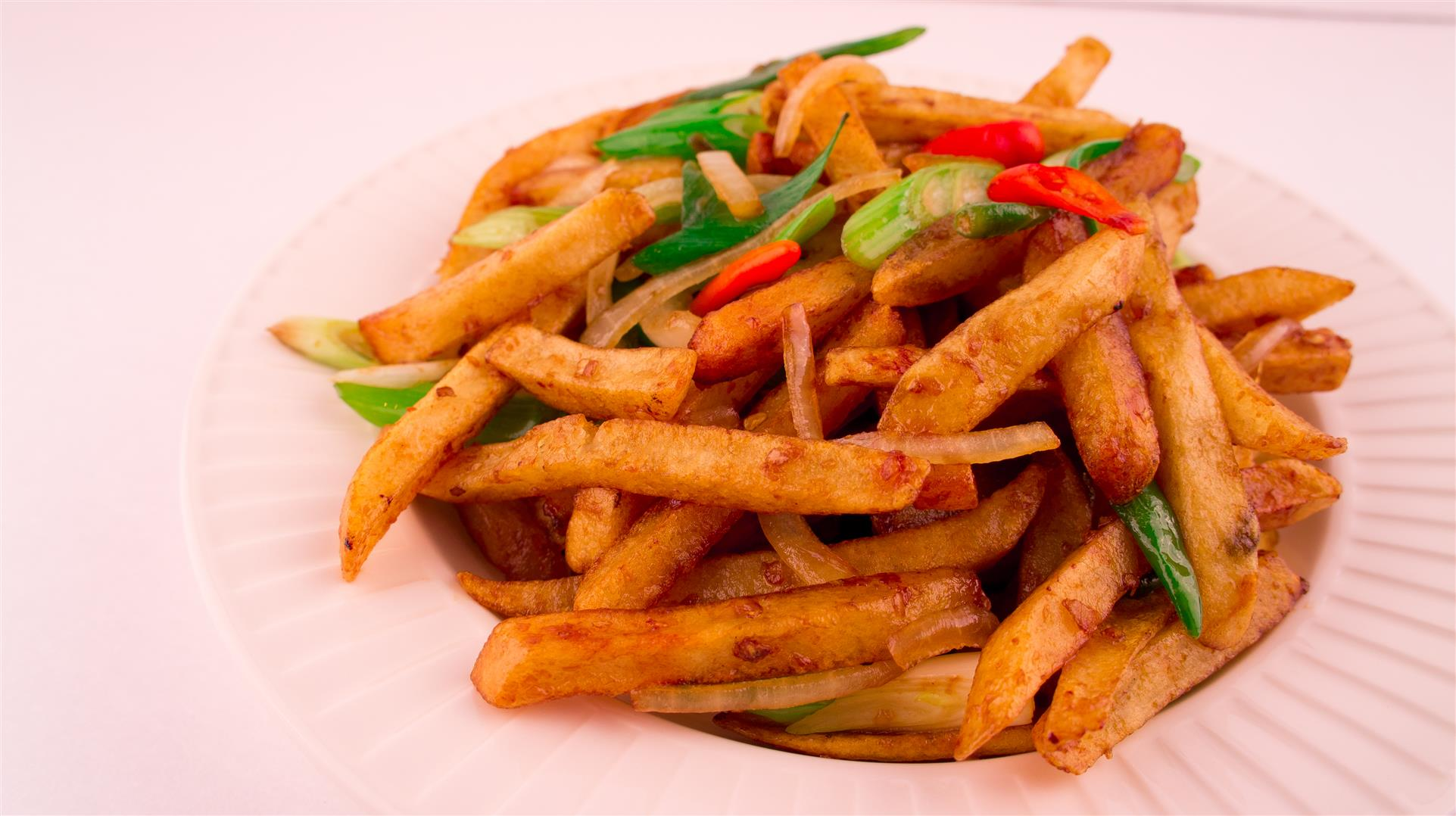 asian-style poutine, with onion, peppers, scallions, and french fries in a sauce