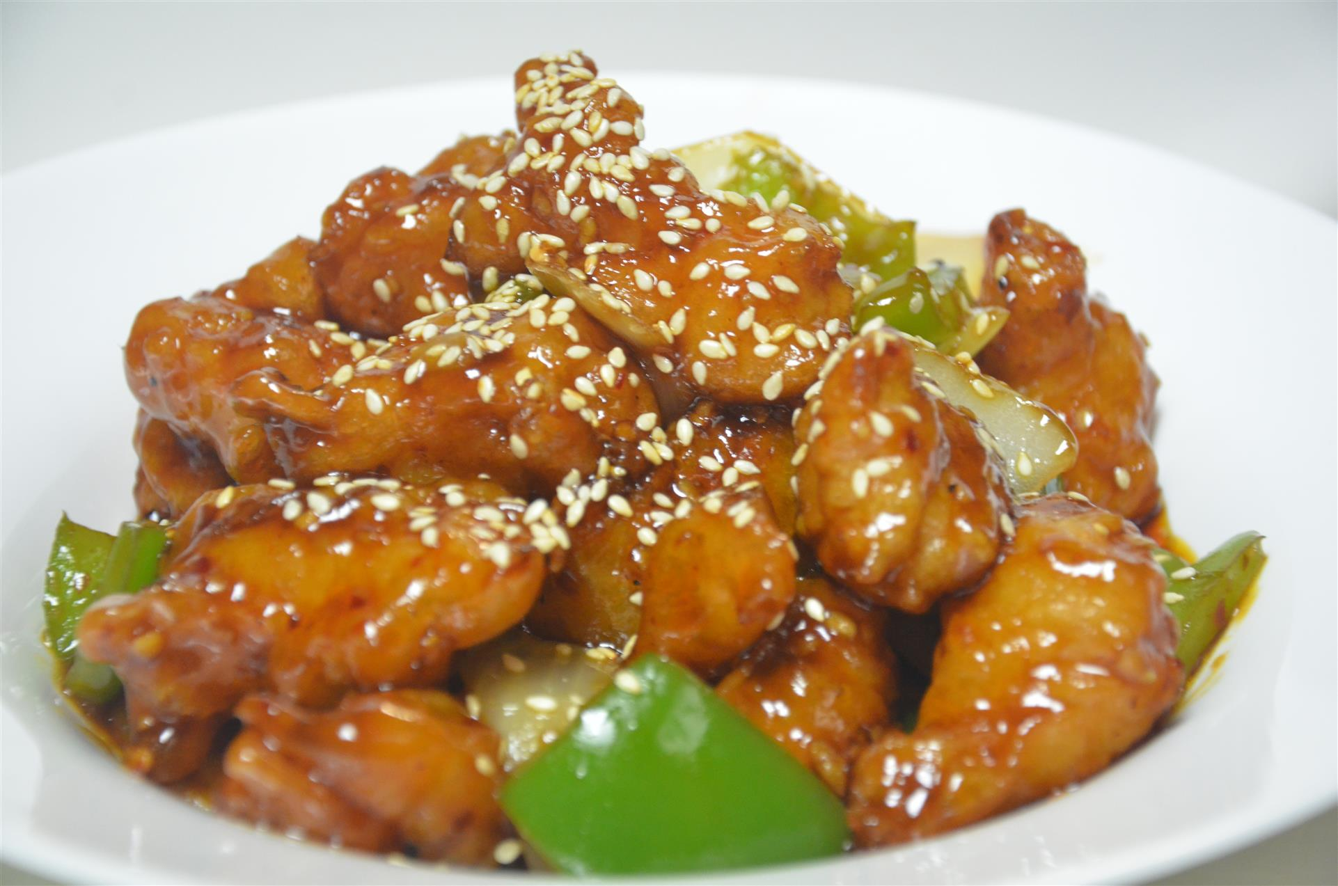 bowl of sesame chicken with bell peppers, onions, and sesame seeds