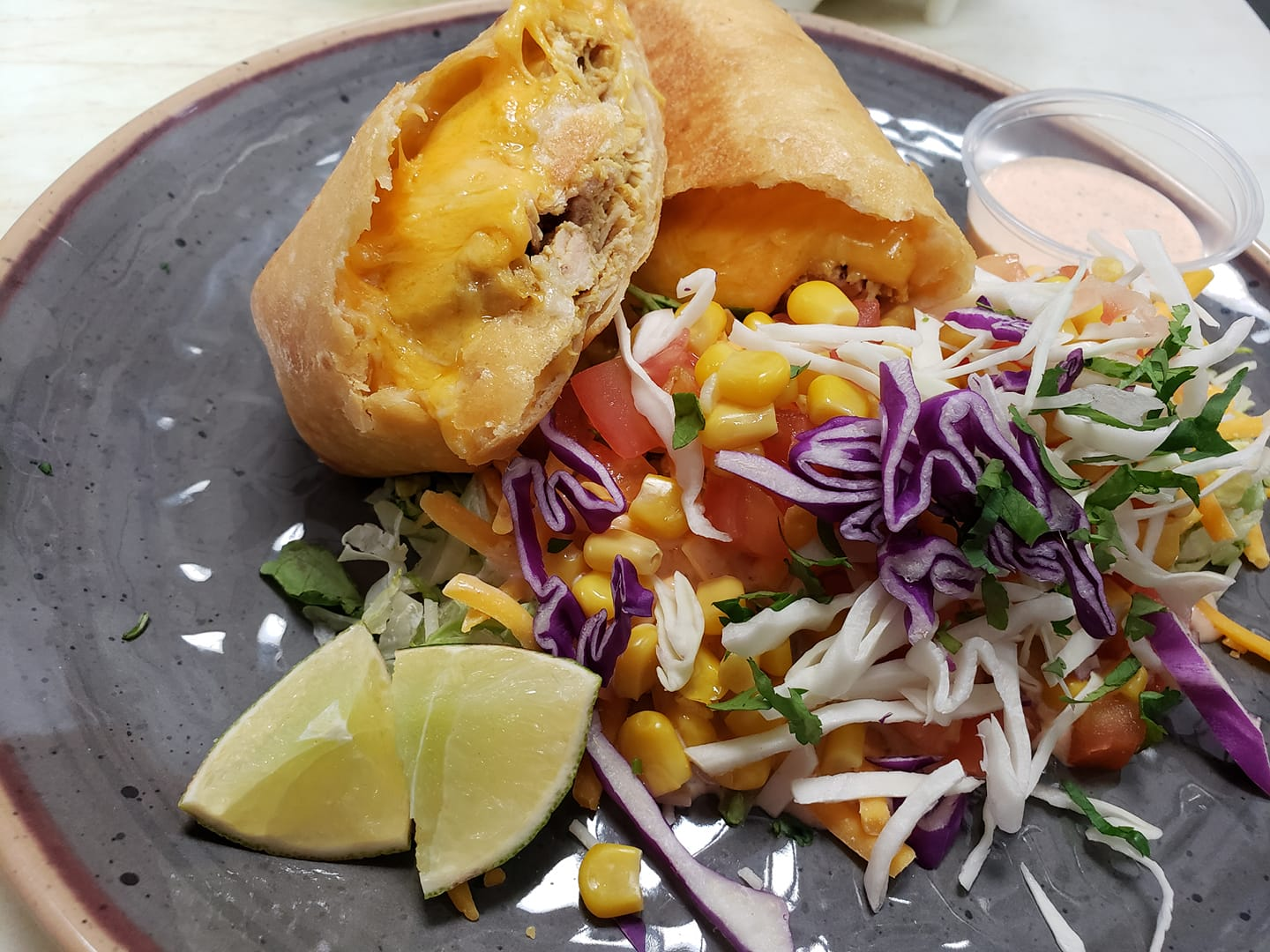 pork and cheese egg rolls served with corn and cabbage slaw