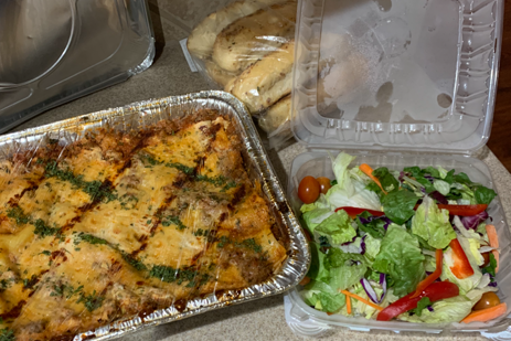A tray of chicken casserole and a house salad to go