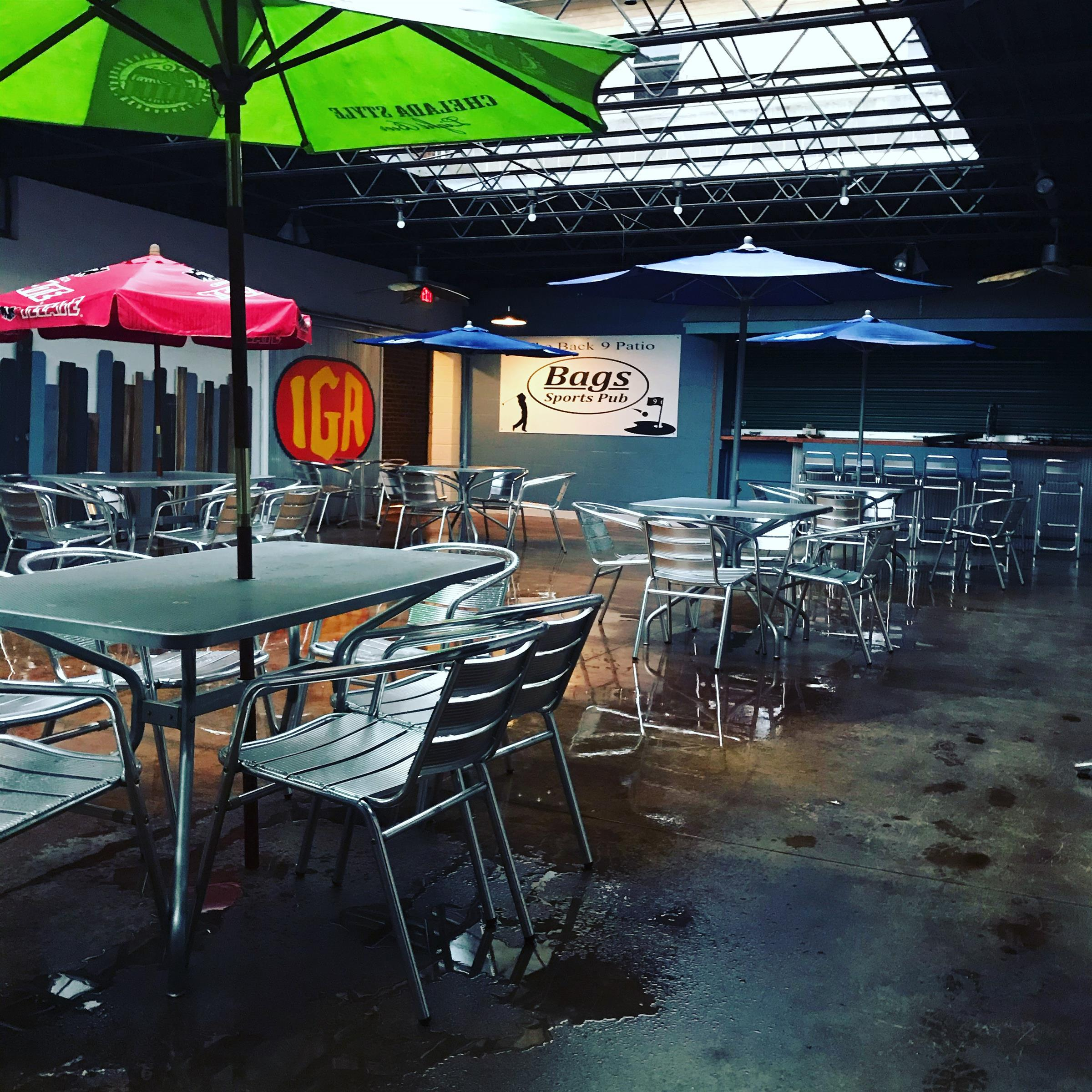 back 9 patio at bags with metal tables and chairs and umbrellas