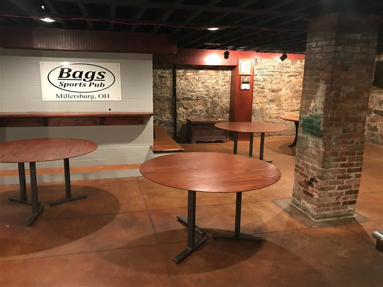 """The Old Stone Cellar"" at Bags, with wooden tables and stone walls"