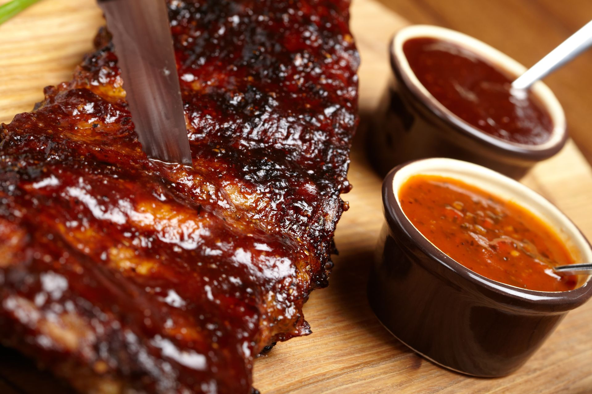 BBQ ribs on a wood table-top with small containers of sauce on the side