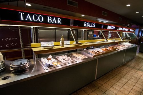 food bar with taco fixings, utensils, and dinner rolls