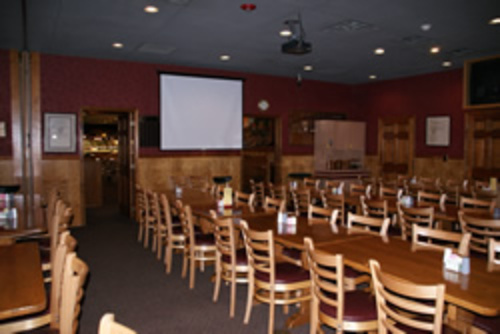 empty banquet room with long tables and chairs, and a large projection screen