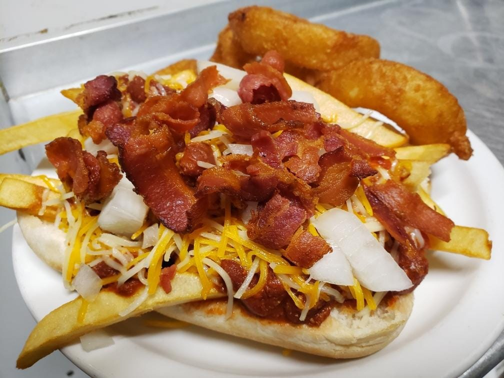 chili dog with fries, cheese, onions, and bacon on top served with onion rings on the side