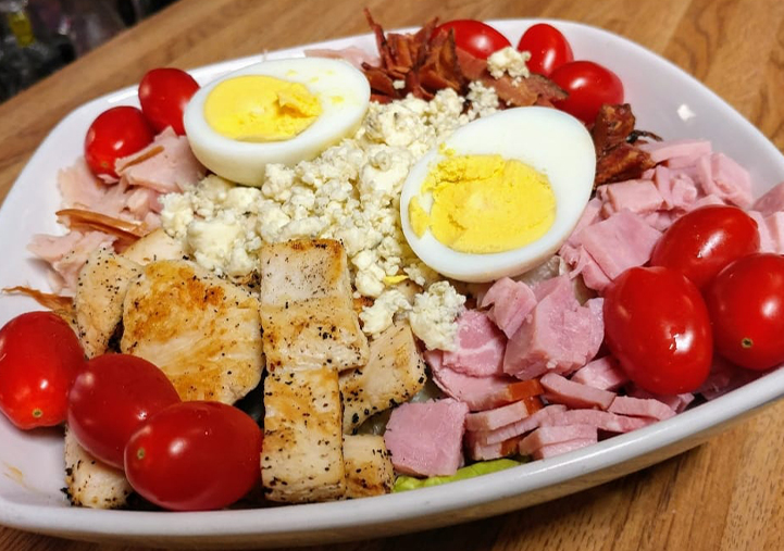 chef salad with lettuce, tomatoes, bacon, chicken, ham, gorgonzola cheese and hard boiled eggs
