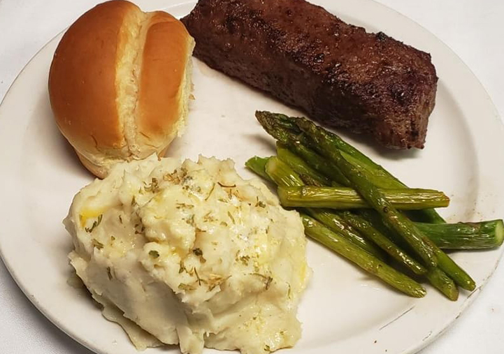 steak, green beans, mashed potatoes and a dinner roll