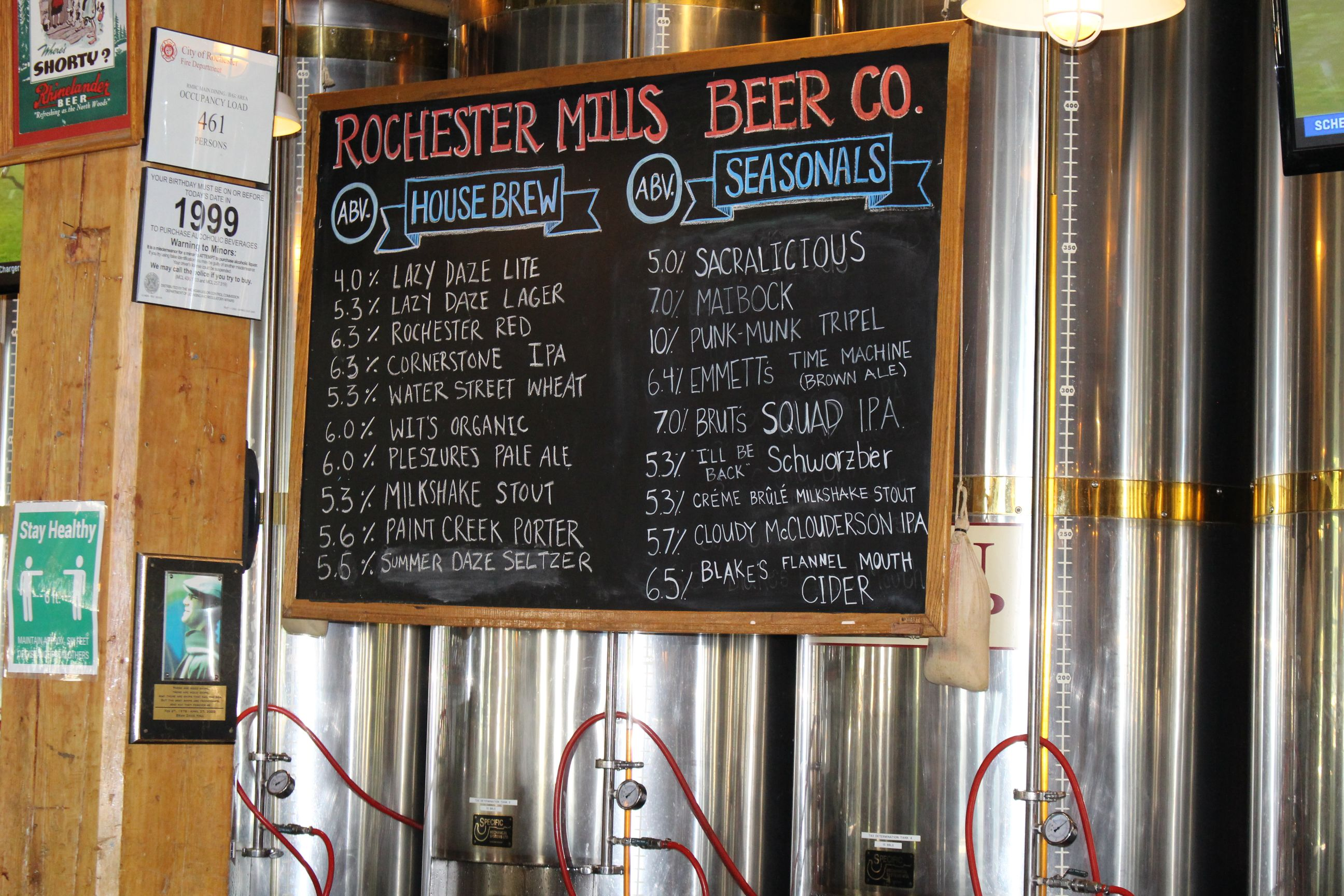 "brewing facility with chalkboard reading ""rochester Mills Beer Co."" with lists of house brews and seasonal beers"