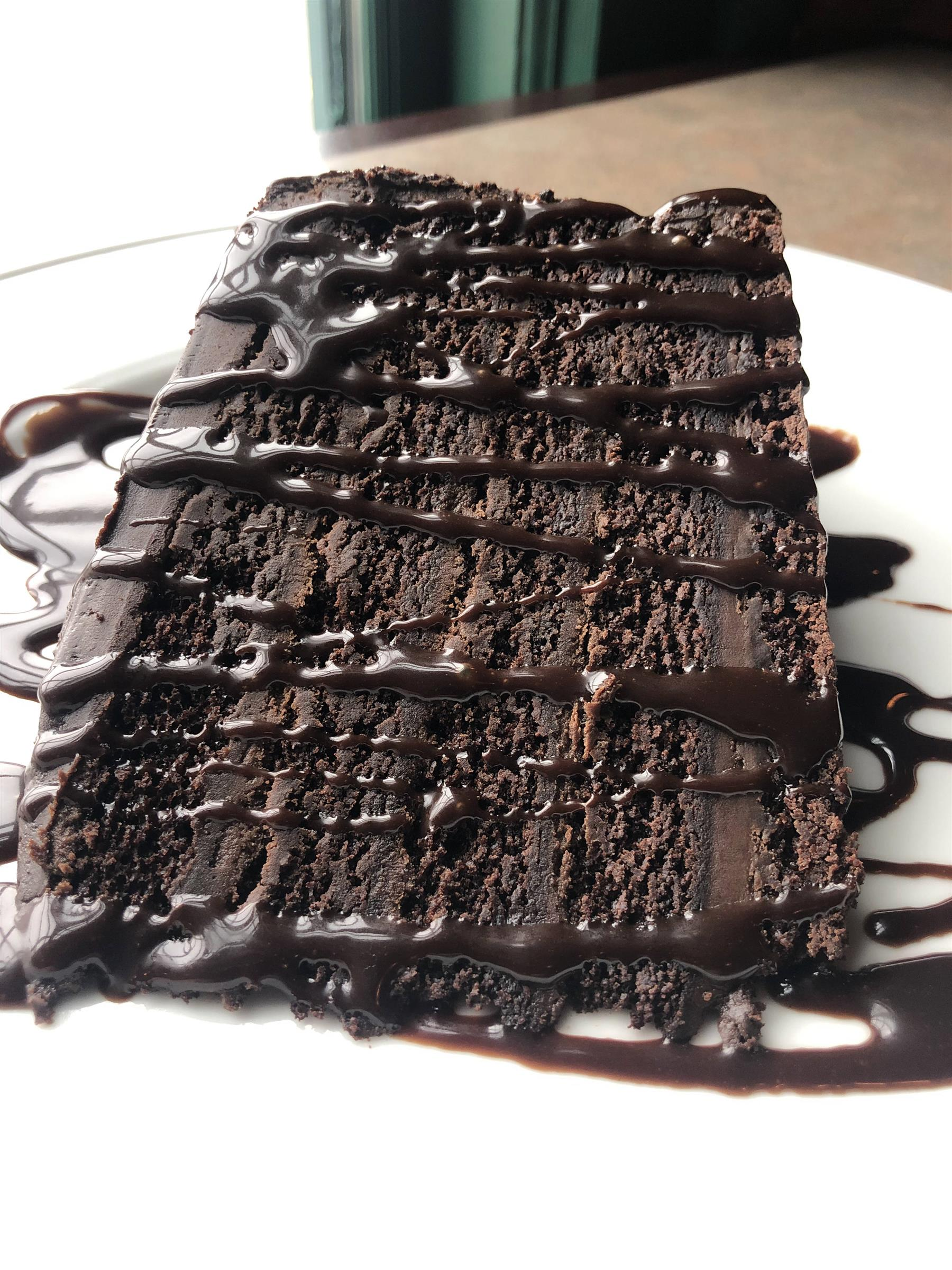 thick slice of chocolate cake with chocolate drizzle