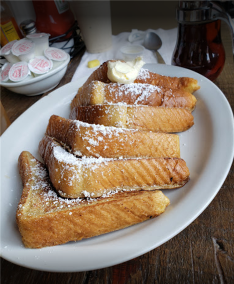 french toast on a plate topped with powdered sugar and a scoop of butter