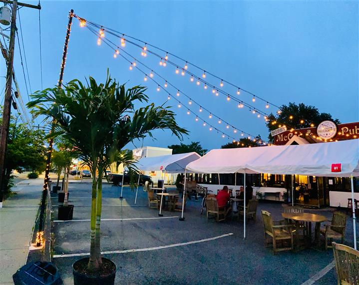 outside dining setup with canopies and lights